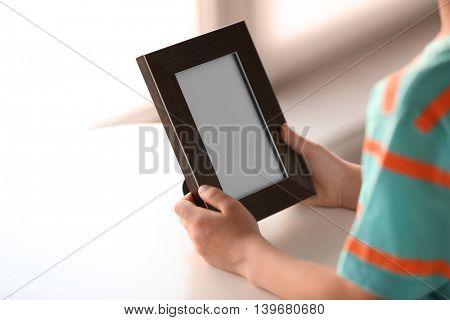 Child's hands holding photo frame on light background