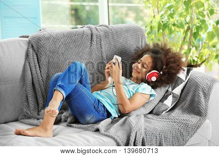 Cute African girl listening music on couch