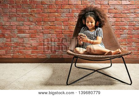 Afro-American little girl with headphones and phone on brick wall background