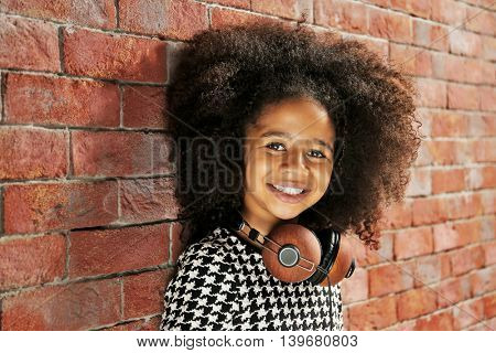 Afro-American little girl with headphones on brick wall background