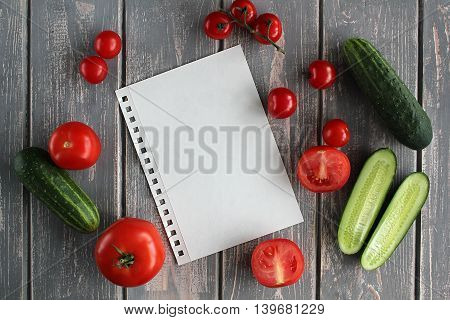 Sheet and composition of vegetables on grey wooden desk. Tomato, cucumber. Top view.