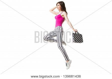 side view of happy brunette model in striped legging and pink with polka dot bag. Isolate.
