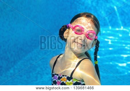 Child swims in pool under water, funny happy girl in goggles has fun and makes bubbles, kid sport on active family vacation