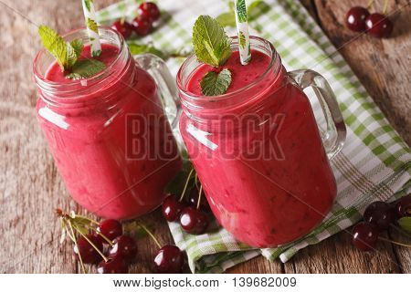 Fresh Cherry Smoothie With Mint In Glass Jars Close-up. Horizontal