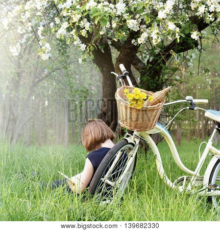girl reading a book resting in the grass of the bike under the blooming fruit trees at sunset