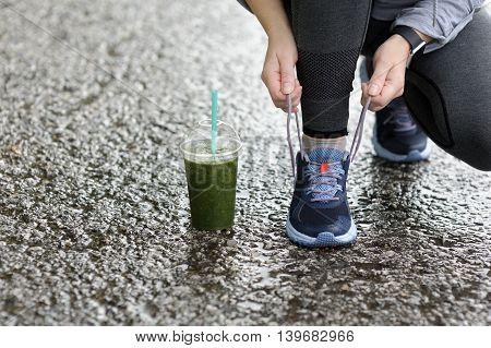 Runner Woman Tying Laces Before Training In The Rain. Marathon.