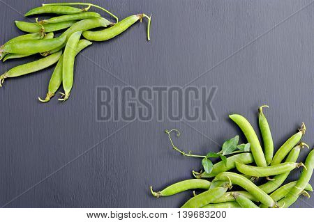 Pods of green peas with leaves on a dark background. Top view. Vitamins. Diet. Summer. Agriculture. Horticulture. Crop.