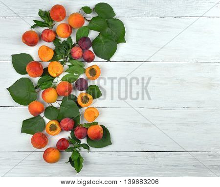Ripe plums and apricots whole and half on old painted wooden background. top view. Summer abundance. Background of bright fruit. Kitchen. Diet. Healthy eating. Rustic style.