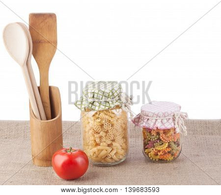 Multicolored pasta in glass jars tied rag covers