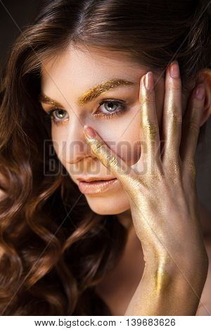 Portrait of beautiful young brunette woman with golden eyebrow and hand looking away