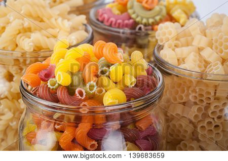 Full round glass jars of pasta. Pasta has a different color