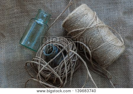 Two glass bottles and threads of the twine and paper tow.