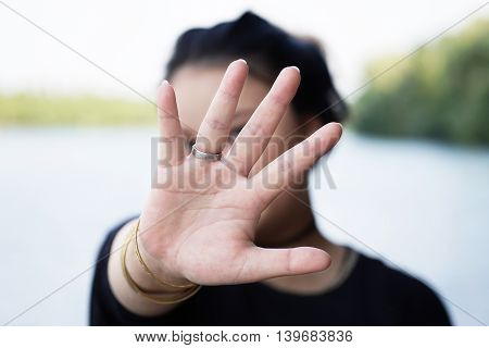woman hiding face behind hand. defense reaction.