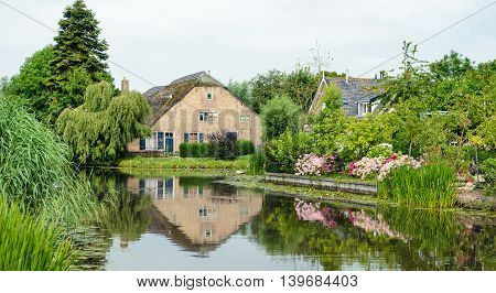 Historic farm reflected in the mirror smooth water surface of a small river in the Netherlands. It is summer and colorful Hydrangea plants are blooming at the banks