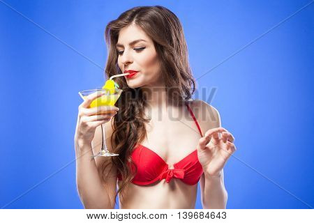 Portrait of cheerful brunette drinking summer cocktail through the straw.Isolate