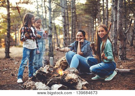Group of kids with mom sitting by the fire and drinking tea in autumn forest, hike at weekend