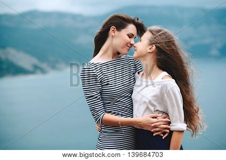 Mom and her teenage daughter hugging and smiling together over blue sea view