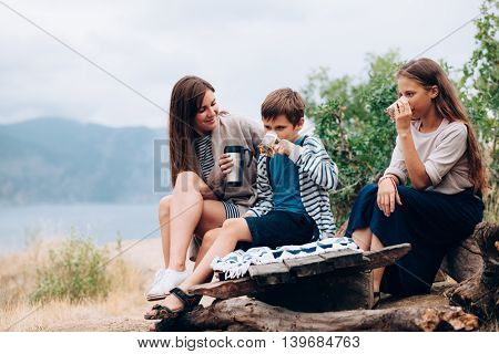 Mom with two preteen children having picnic outdoor, cool autumn weather