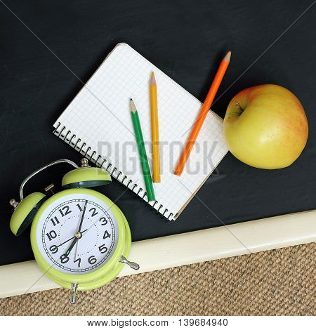 background with flat lay mechanical watches colored pencils autumn apple on the blackboard / Back to School