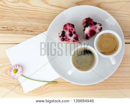 background with coffee and berry cake in the form of hearts top view / delicious holiday dish for couples