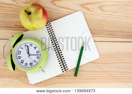 watches notepad pencil and apple on wooden background top view/time to eat