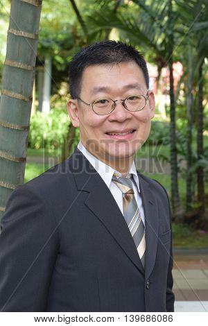 An asian business man smiling at the woods
