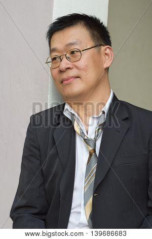 Portrait of a laid back mature asian business man resting