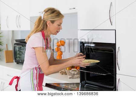 woman doing baking placing a cake in the oven