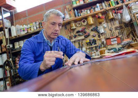 happy senior male carpenter marking on wood