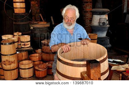 Mystic Connecticut - July 11 2015: Cooper at work making a wooden barrel in the Cooperage Shop at Mystic Seaport Museum