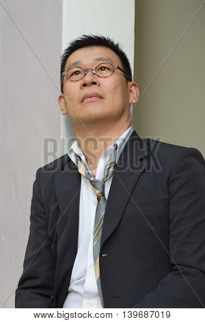 Portrait of a laid back mature asian business man looking at the sky with soft tears in eyes