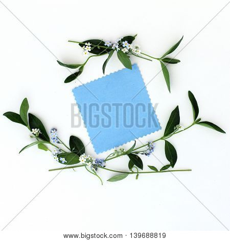 flat lay background with spring flowers as a frame and blank sheet for congratulations top view/ congratulatory background with flowers