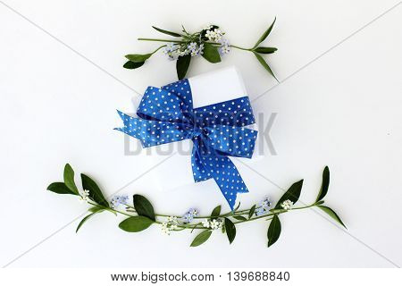Wilde background with flowers and celebratory gift bandaged blue ribbon polka dot top view / Holiday gift background