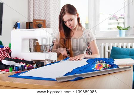 Woman Cutting Pattern From Fabric