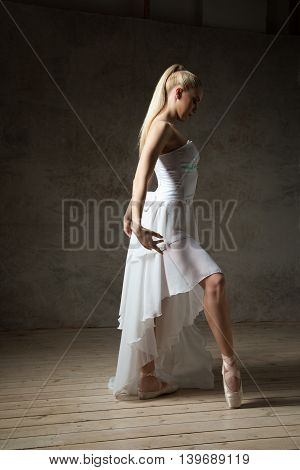 Side view of beautiful blonde ballet dancer with hair in tail posing in studio