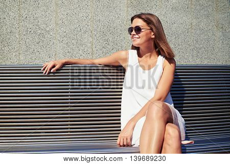 Young smiling beautiful woman in sunglasses is sitting on a bench near the building wall on a sunny summer day