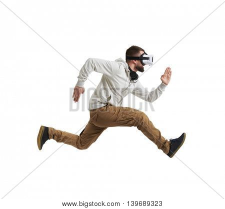 Young man in virtual reality headset is photographed in mid-air jump isolated on white background