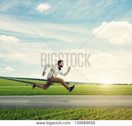Young man in casual clothes is running violently on the background of green meadow during sunset