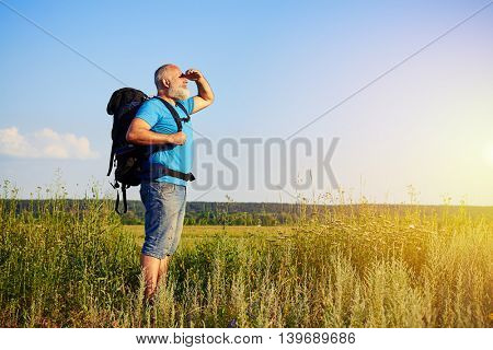 Physically fit handsome aged man with rucksack is standing in the grass and looking at sunlight