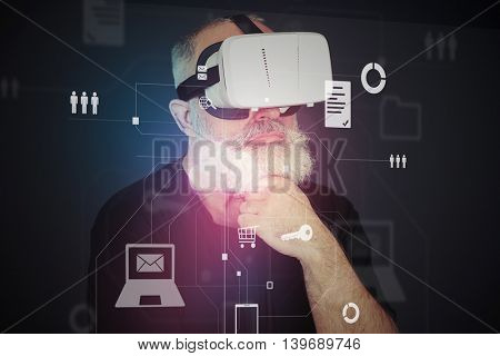 Aged man with white beard in virtual reality headset is standing in front of interactive screen with different icons and thinking about something