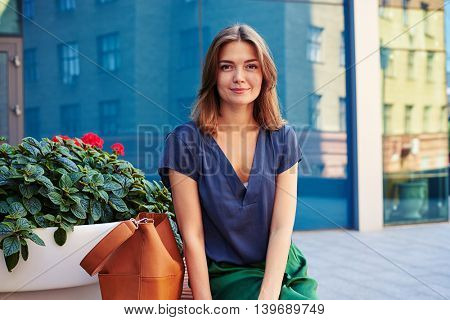 Close-up of charming smiling elegant woman sitting on bench with flower pot on the background of mirror glass modern building