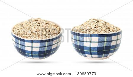 Uncooked oatmeal in a bowl, dry oat flakes isolated on white background