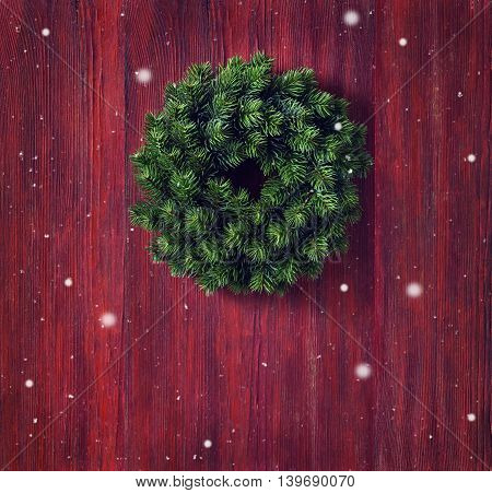 Christmas wreath on old red wooden background.