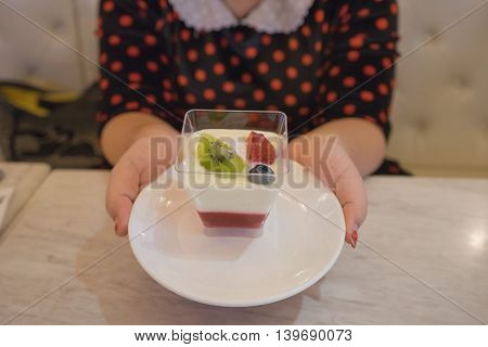 woman hand holding strawberry yogurt in a sweet or dessert shop on marble table