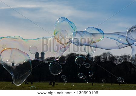 Group of Differently Sized Bubbles Floating on Top of Munich Landscape