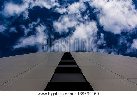 Close-Up View of Tiled Wall Outdoors Leading to Deep Blue Sky and Clouds