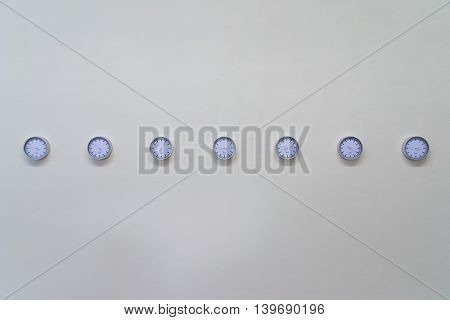 Seven Clocks Hanging in Row on Plain White Wall
