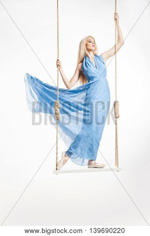 Portrait of beautiful young ballerina standing on swings in blue dress and pointes.Isolated.