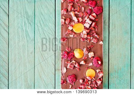 Top view of an orange strawberry and raspberry milk chocolate tablet on a light teal wooden background.