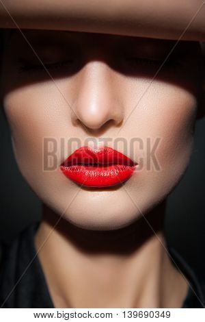 Close-up of young model with eyes closed, red lips and perfect smooth skin in flash light